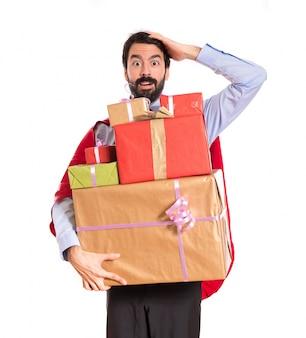 Hombre de negocios de la sorpresa vestido como superhéroe que sostiene los regalos