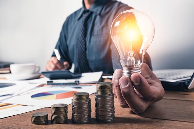 Hombre de negocios sosteniendo una bombilla con monedas dinero y copia espacio para contabilidad, ideas y concepto creativo.