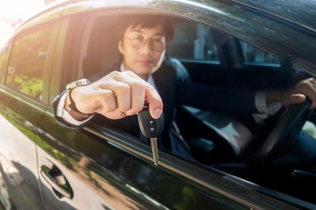 El hombre de negocios está sosteniendo el coche dominante en el coche