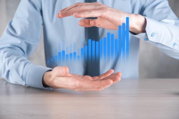 Hombre de negocios sosteniendo un gráfico con crecimiento positivo de beneficios. planificar el crecimiento del gráfico y el aumento de los indicadores positivos del gráfico
