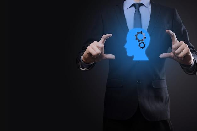 Hombre de negocios sosteniendo un icono de hombre con engranajes en su cabeza. inteligencia artificial. avances tecnológicos. robot. símbolo de contorno.
