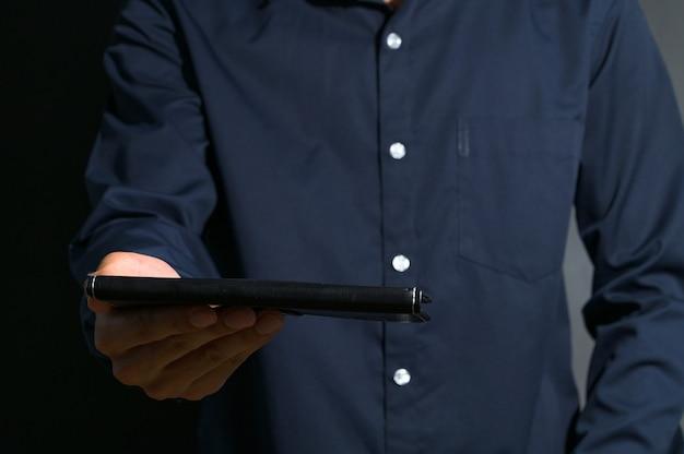 Un hombre de negocios sosteniendo un libro negro.