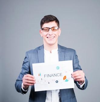 Hombre de negocios sosteniendo papel con inscripción de finanzas y sonriendo