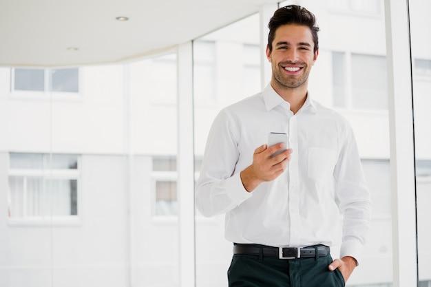 Un hombre de negocios está sosteniendo su teléfono inteligente y sonriendo