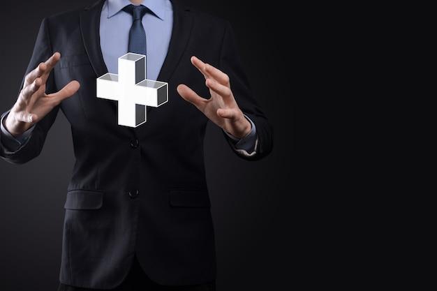 El hombre de negocios sostiene el icono 3d plus, el hombre sostiene en la mano ofrece algo positivo como ganancias, beneficios, desarrollo, rse representado por el signo más. la mano muestra el signo más