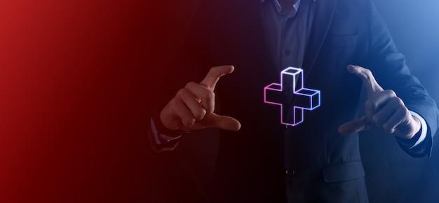 El hombre de negocios sostiene el icono 3d plus, el hombre sostiene en la mano ofrece algo positivo como ganancias, beneficios, desarrollo, rse representado por el signo más. la mano muestra el signo más.