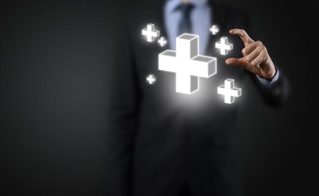 El hombre de negocios sostiene el icono 3d plus, el hombre sostiene en la mano ofrece algo positivo como ganancias, beneficios, desarrollo, rse representado por el signo más.