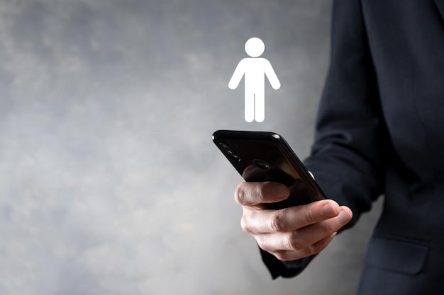 Hombre de negocios sostiene el icono de la persona del hombre en el fondo de tono oscuro. hr humano, icono de la gente negocio del sistema de proceso de la tecnología con el reclutamiento, la contratación, la formación de equipos. concepto de estructura organizativa.