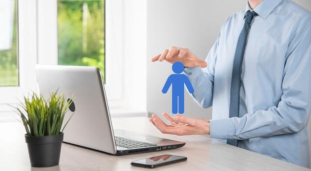 Hombre de negocios sostiene el icono de la persona del hombre en el fondo de tono oscuro. hr humano, icono de la gente negocio del sistema de proceso de la tecnología con el reclutamiento, la contratación, la formación de equipos. concepto de estructura organizativa