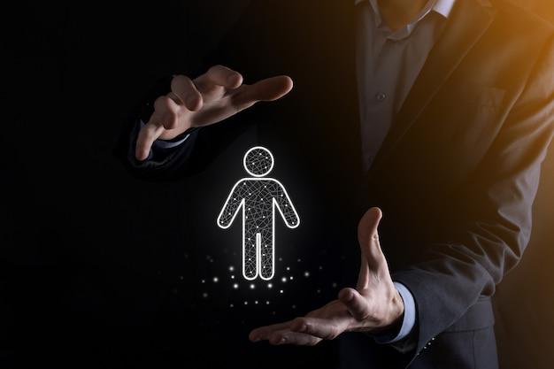 Hombre de negocios sostiene el icono de la persona del hombre en la pared de tono oscuro. hr humano, icono de la gente. concepto de estructura organizativa.