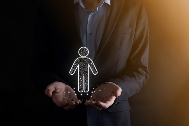 Hombre de negocios sostiene el icono de la persona del hombre en la pared de tono oscuro. hr humano, icono de la gente negocio del sistema de proceso de la tecnología con la contratación, la contratación, la formación de equipos. concepto de estructura organizativa.