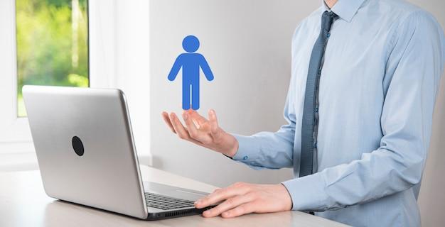 Hombre de negocios sostiene el icono de la persona del hombre en la superficie de tono oscuro. hr humano, icono de la gente negocio del sistema de proceso de la tecnología con el reclutamiento, la contratación, la formación de equipos.