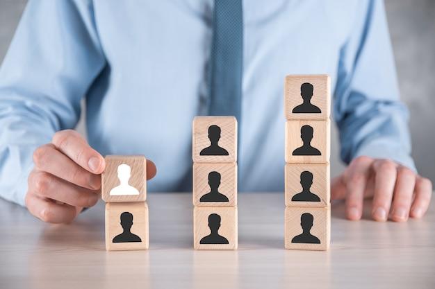 El hombre de negocios sostiene y pone la forma del bloque del cubo de madera con el icono del usuario en la tabla gris. espacio para texto. primer plano de la interfaz de los iconos de internet. concepto de medios de red global, contacto en pantallas virtuales, espacio de copia