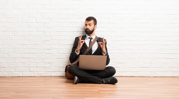 Hombre de negocios con su computadora portátil que se sienta en el piso orgulloso y satisfecho en amor usted mismo concepto