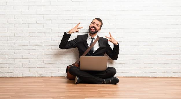 Hombre de negocios con su computadora portátil que se sienta en el piso que muestra la lengua en la cámara que tiene mirada divertida