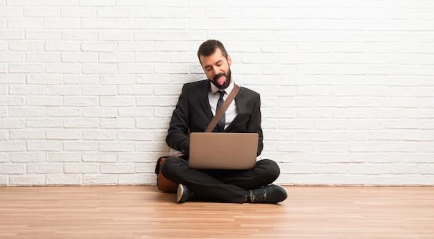 Hombre de negocios con su computadora portátil sentada en el piso mostrando la lengua en la cámara con aspecto divertido