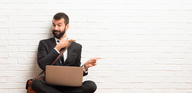 Hombre de negocios con su computadora portátil sentada en el suelo apuntando el dedo hacia un lado en posición lateral