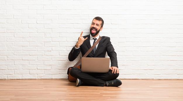 Hombre de negocios con su computadora portátil sentada en el suelo mostrando la lengua y sacando los cuernos