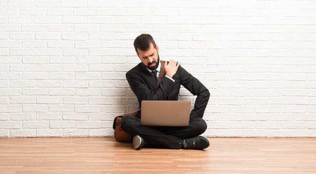 Hombre de negocios con su computadora portátil sentada en el suelo sufriendo dolor en el hombro por haber hecho un esfuerzo
