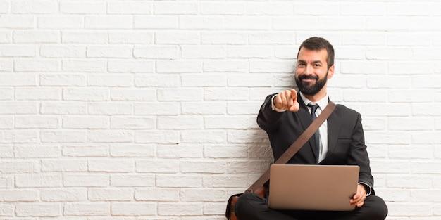 El hombre de negocios con su computadora portátil sentado en el piso apunta con el dedo hacia ti con una expresión de confianza