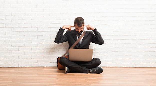 Hombre de negocios con su computadora portátil sentado en el suelo cubriendo ambas orejas con las manos