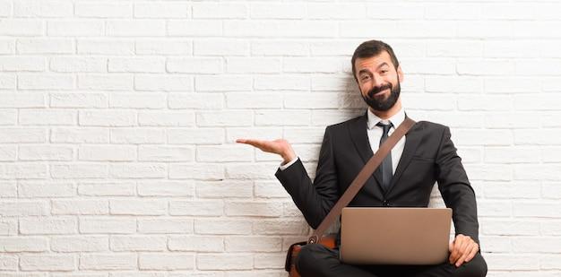 Hombre de negocios con su computadora portátil sentado en el suelo sosteniendo copyspace imaginario en la palma para insertar un anuncio