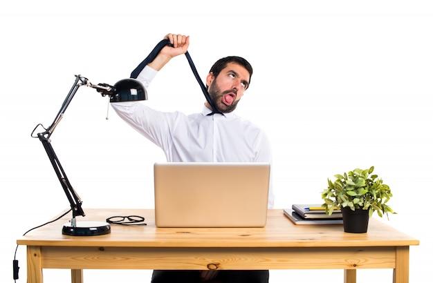 Hombre de negocios en su oficina ahogándose