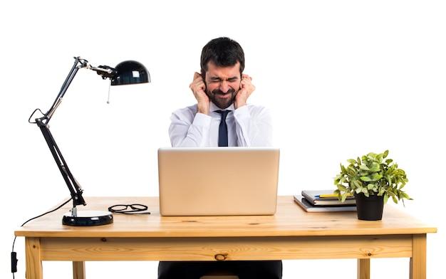 Hombre de negocios en su oficina cubriendo sus oídos