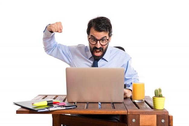 Hombre de negocios en su oficina dando puñetazo sobre fondo blanco