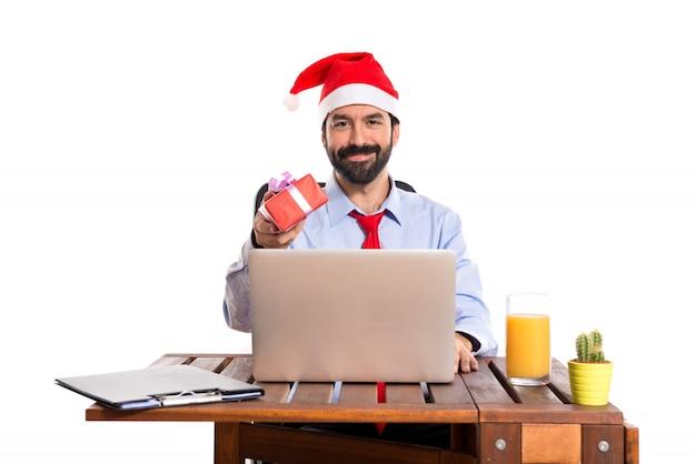 Hombre de negocios en su oficina dando un regalo