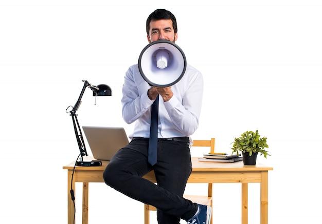 Hombre de negocios en su oficina gritando por megáfono