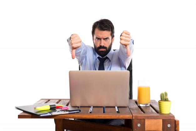 Hombre de negocios en su oficina haciendo una mala señal