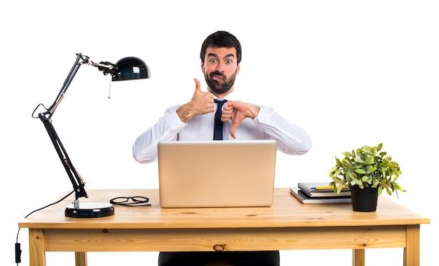 Hombre de negocios en su oficina haciendo signo bueno-malo