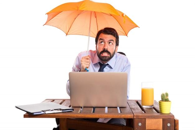 Hombre de negocios en su oficina con un paraguas