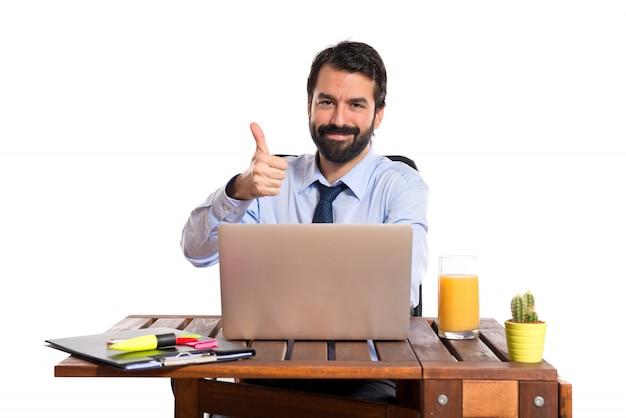 Hombre de negocios en su oficina con el pulgar para arriba