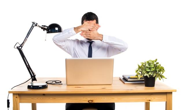 Hombre de negocios en su oficina que cubre su cara