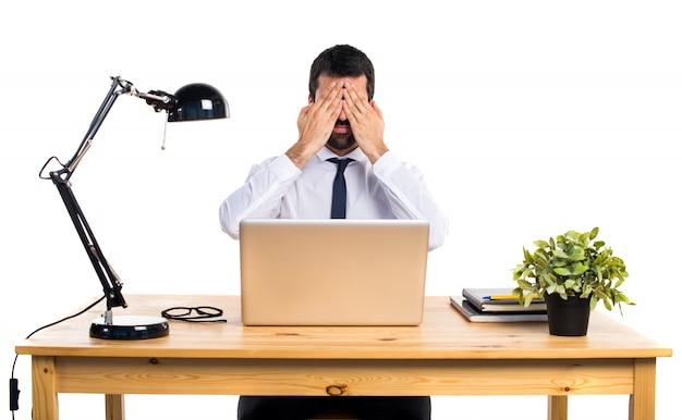 Hombre de negocios en su oficina que cubre sus ojos