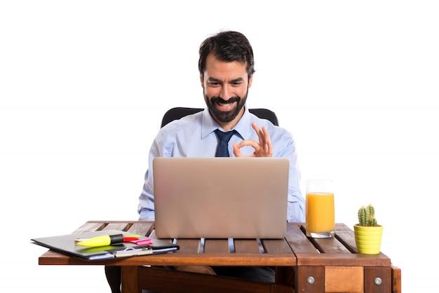 Hombre de negocios en su oficina que hace la muestra aceptable