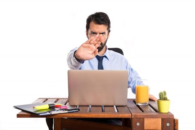 Hombre de negocios en su oficina que hace la señal de la parada