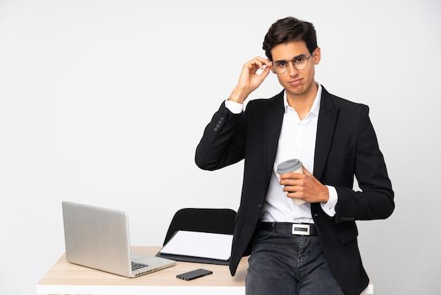 Hombre de negocios en su oficina sobre la pared blanca aislada infeliz y frustrado con algo. expresión facial negativa