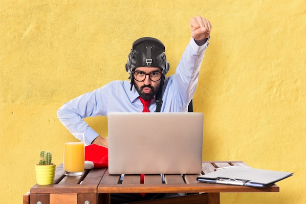 Hombre de negocios en su oficina con el sombrero del piloto