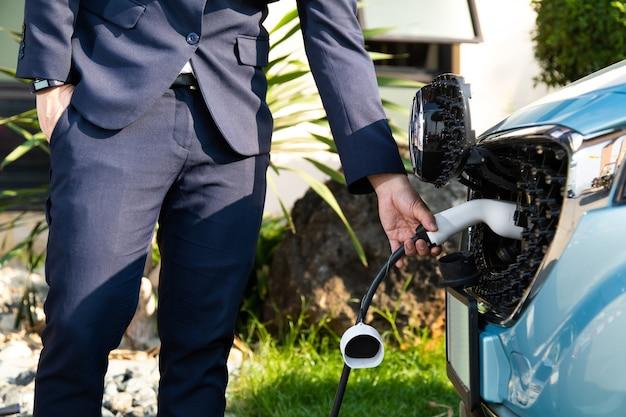 Hombre de negocios en suite mientras carga el coche eléctrico