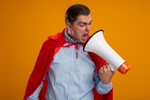 Hombre de negocios de superhéroe enojado en capa roja gritando al megáfono con expresión agresiva de pie sobre fondo naranja