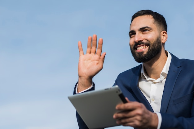 Hombre de negocios con tableta agitando