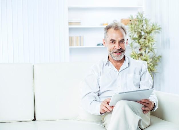 Hombre de negocios con tableta digital sentado en el sofá en la oficina luminosa.