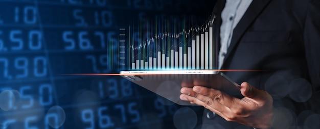 Hombre de negocios con tableta con gráfico comercial. gráfico de análisis de marketing bursátil. información estadística diagrama beneficio. concepto de inversión y marketing.