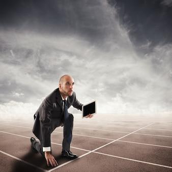 Hombre de negocios con tableta lista para correr en la pista