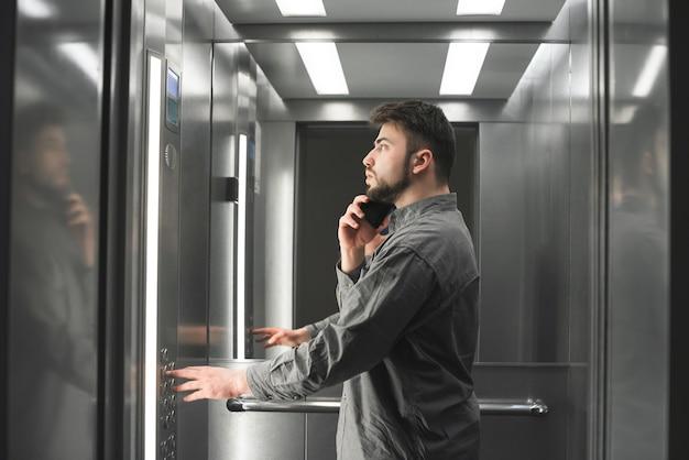 El hombre de negocios está por teléfono en el ascensor presionando el botón.