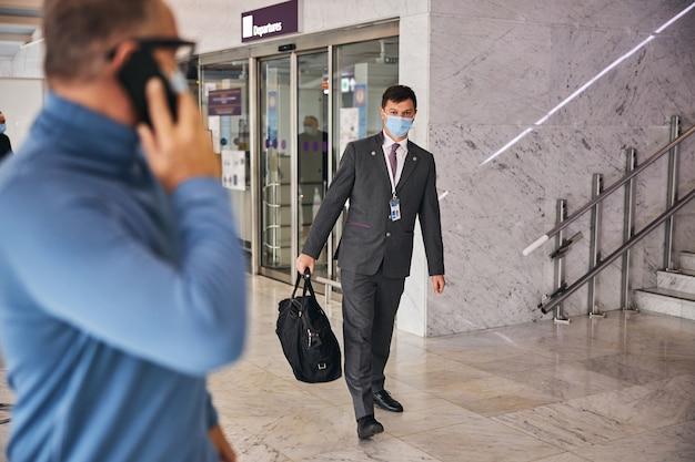 Hombre de negocios con un teléfono mirando al empleado del aeropuerto
