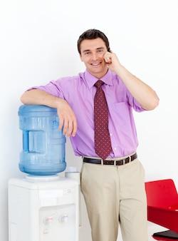 Hombre de negocios en el teléfono por el refrigerador de agua